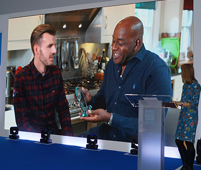 Ainsley Harriot and Alex Pepper on screen at the People Awards 2019
