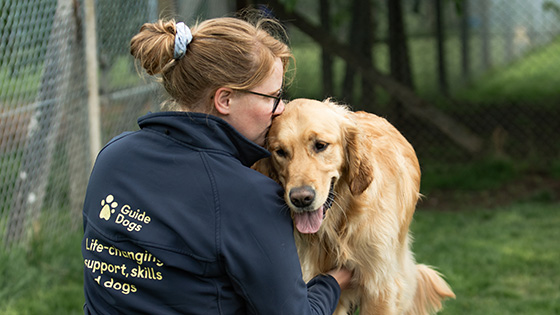 Guide Dogs staff member cuddling a guide dog