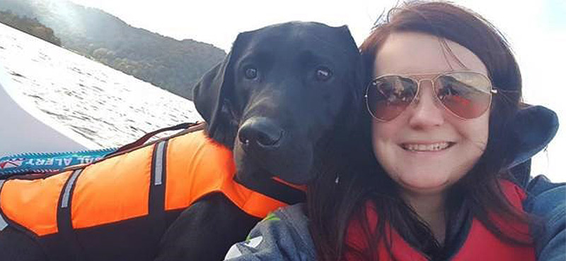 Winner Megan and her dual assistance dog Rowley smile on a boat