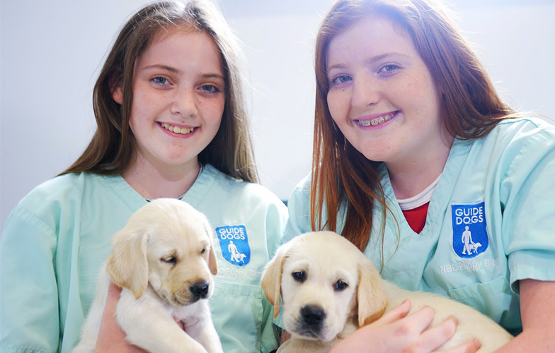 Two young girls smiling and holding puppies at the Guide Dogs National Breeding Centre