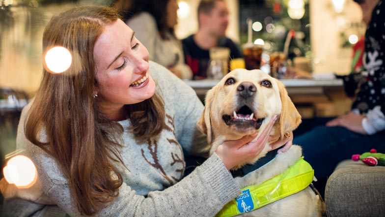 Woman looks happily at her yellow Labrador guide dog