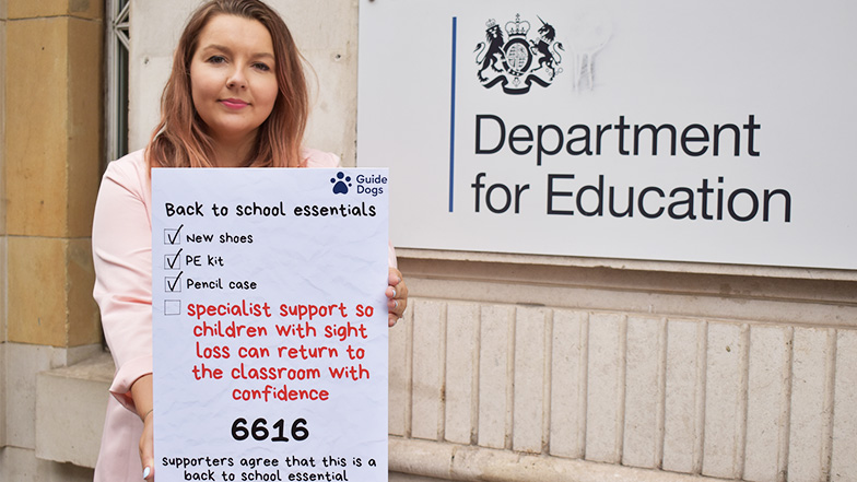 Guide Dog's staff member campaigns for back to school petition outside department of education