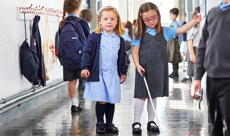Nell holds a cane by her friend's side in school corridor