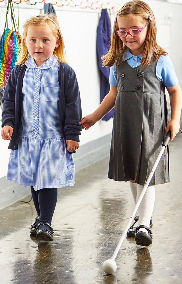 Nell at school using her cane and holding her friend's arm