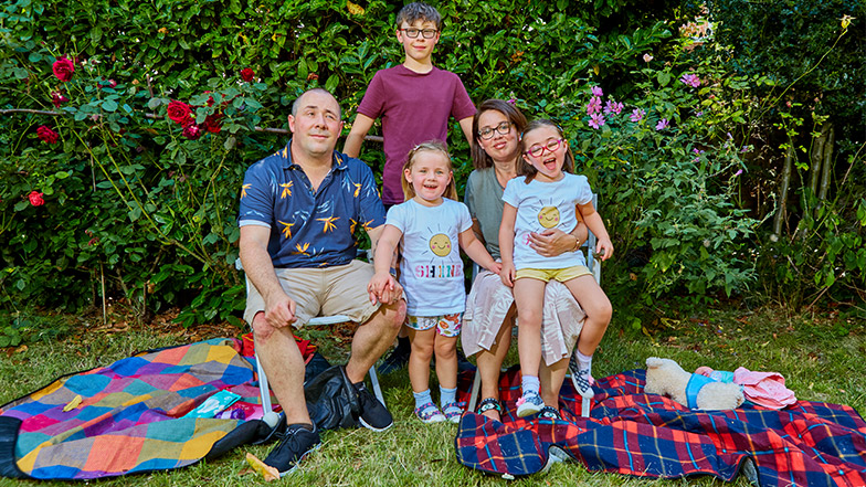 Nell and her mother, father, sister and brother smile happily together in their garden