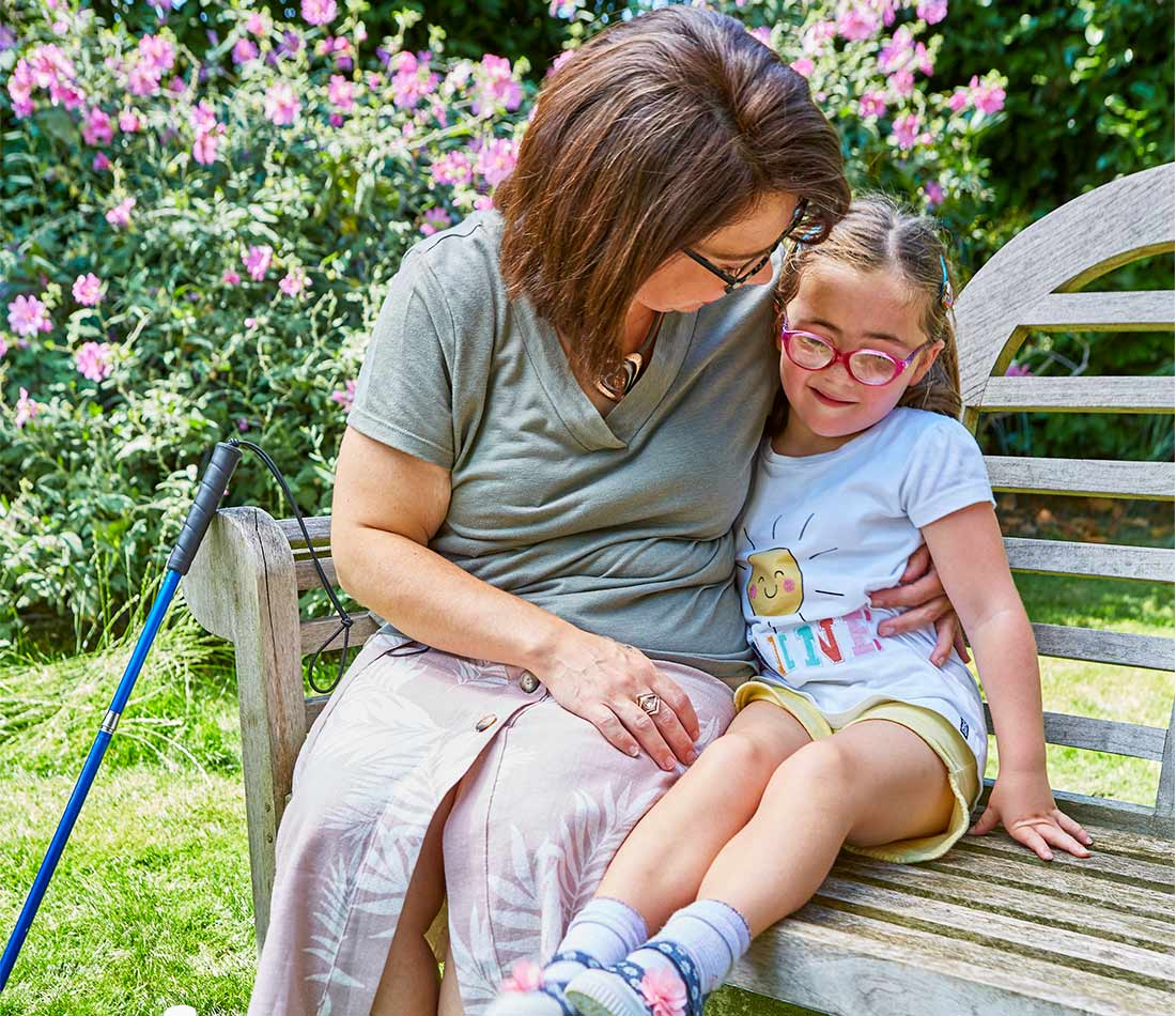 Nell's mum hugs Nell on a bench in their garden