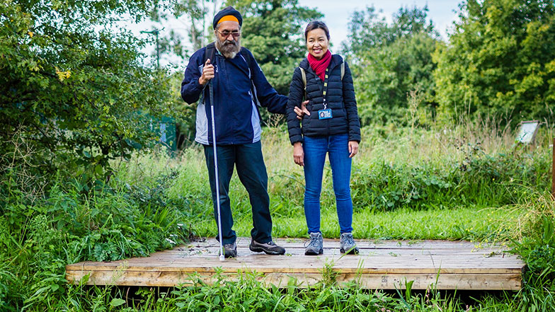 Pardeep with his sighted guide Sophia overlooking the lake