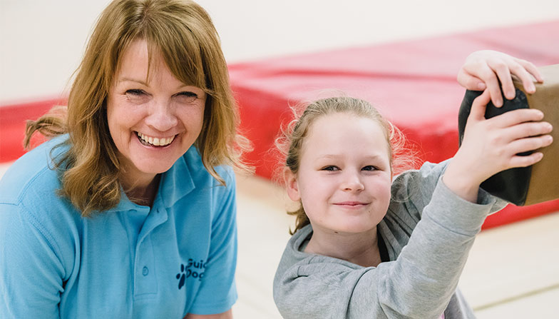 Osahia smiles with her support worker next to her whilst at gymnastics practice
