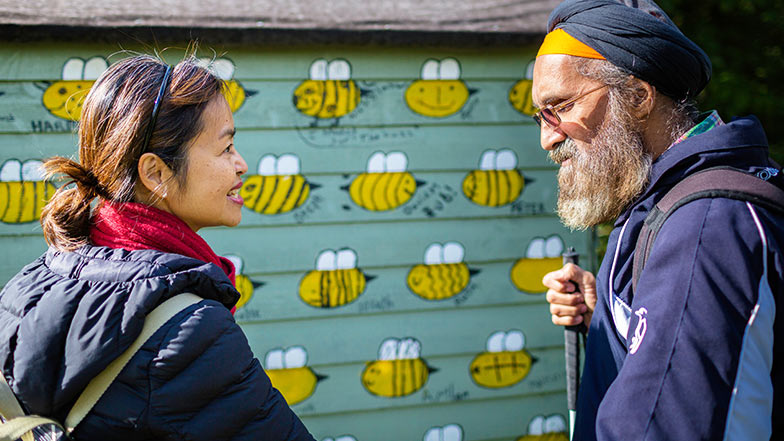 Pardeep who has sight loss is with his my guide volunteer Sophia smiling next to a shed painted with bees