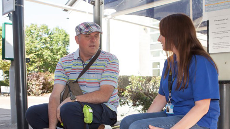 Blind man talking to guide dogs volunteer at a bus stop