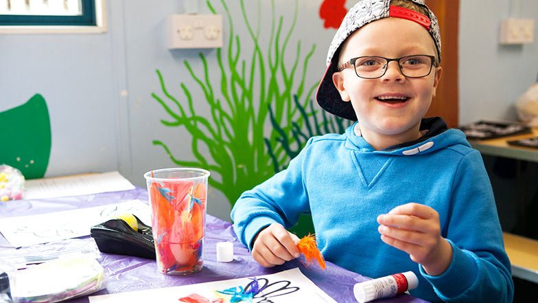 A boy smiles whilst colouring in