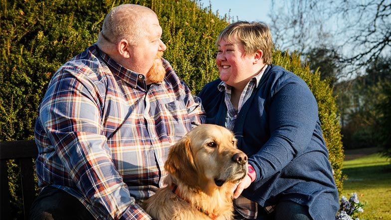 A service user and his wife sit smiling with their guide dog