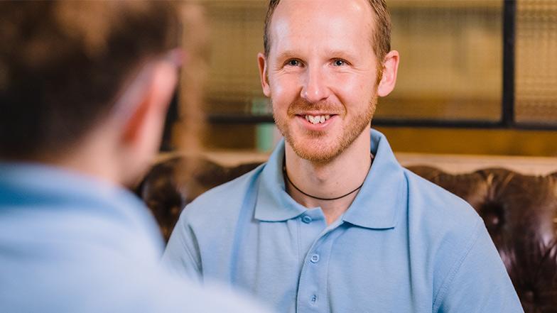 Male volunteer smiles opposite another volunteer