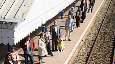 Guide dog owner and guide dog standing with other commuters on a train platform