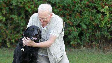 Guide dog owner hugging his guide dog