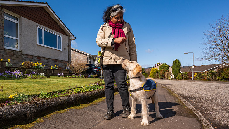 Volunteer puppy raiser Nimmi walks guide dog puppy along pavement on a sunny day
