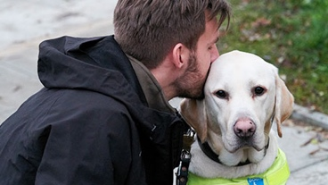 A man embracing his guide dog