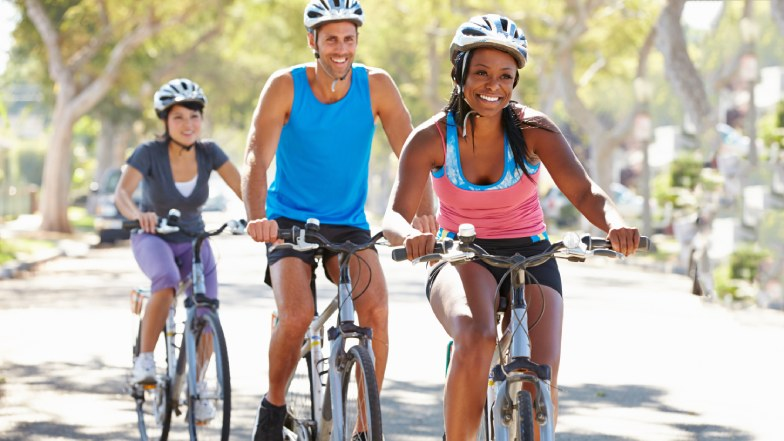 A family cycling wearing helmets