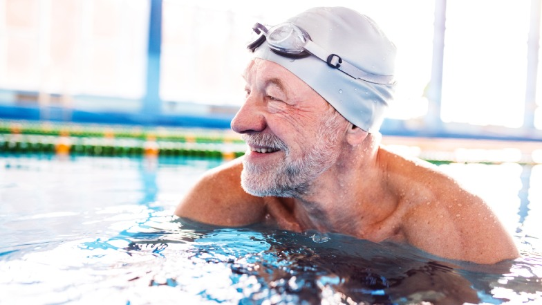 A man in a pool wearing a swimming hat