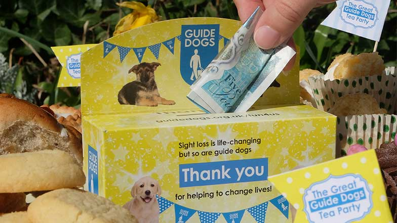 Guide Dogs collecting box with money being put in the slot