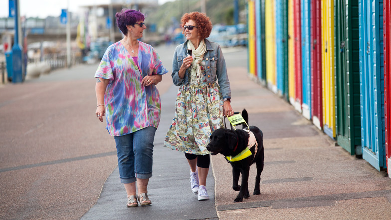Two ladies walking down a beach promenade with their guide dog
