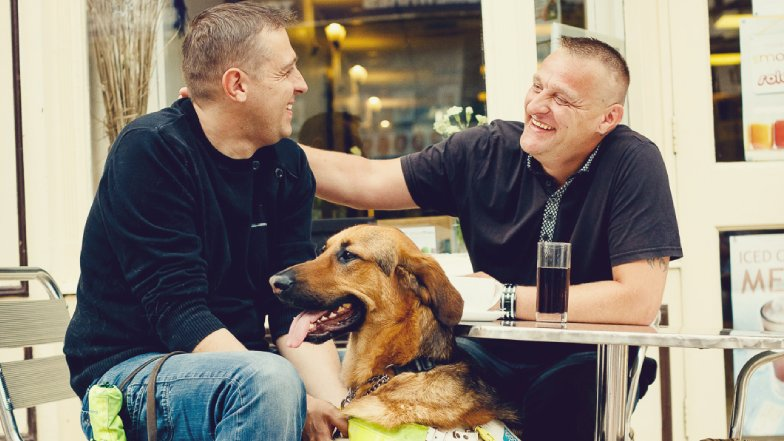 Steve Bowles with his guide dog and a friend at a cafe