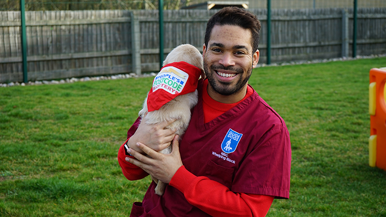 People's Postcode Lottery Presenter Danyl Johnson holding player-funded puppy Ziggy