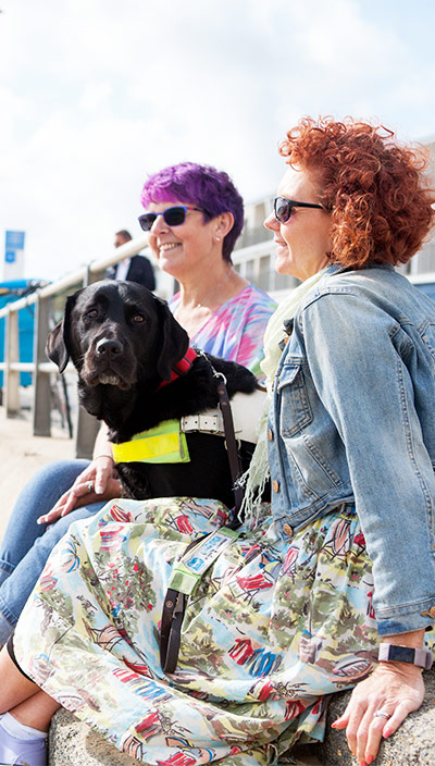 Two women sit on a beach with a black Labrador guide dog between them