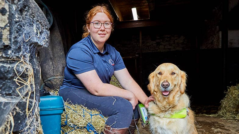 Ella and guide dog Katie sitting together in a barn