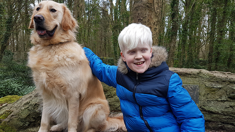 Ellis patting his buddy dog, Ralph, in a forest