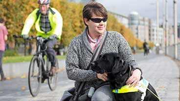 Guide dog owner crouching down next to his guide dog