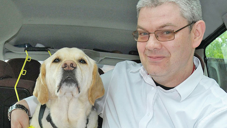 Guide dog owner and his guide dog sitting in a car