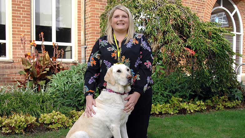 Guide dog owner sitting with her guide dog