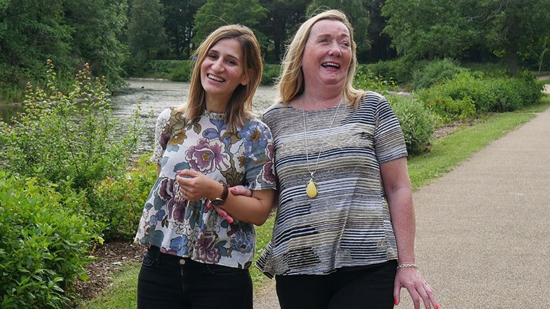 Norma and sighted guide Evi walking outside in a park