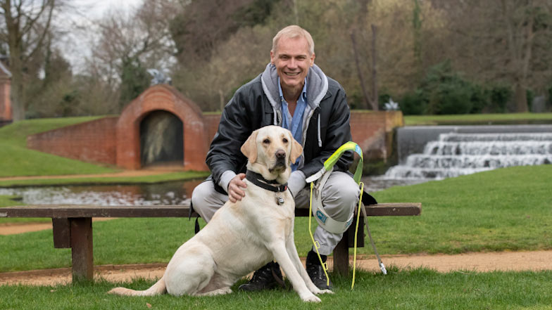 Paul sitting with guide dog Bolt on a bench alongside a waterway