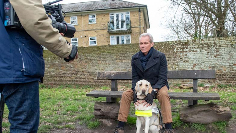 Paul sitting on a bench with guide dog Bolt at his feet