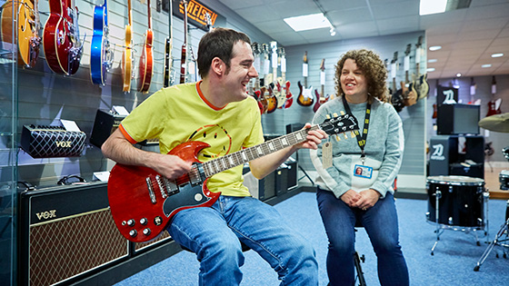 Rik playing the guitar with sighted guide Louise