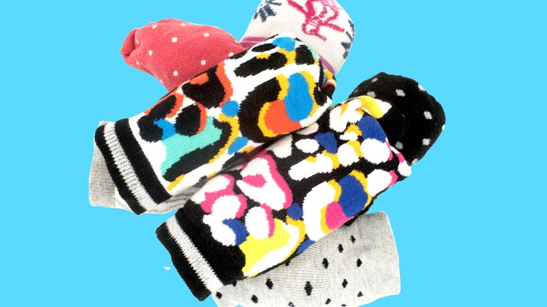A pile of multi-coloured Walk Your Socks Off socks