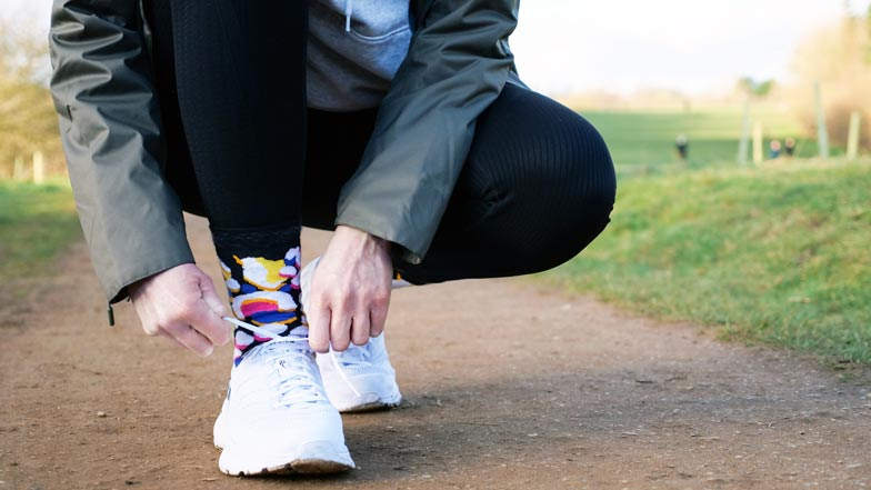 A person bending down tying up their shoe laces with Walk Your Socks Off socks