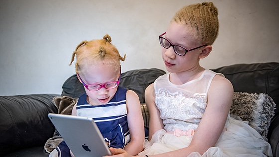 Kamsi and her sister, Nnenna, playing on their iPad