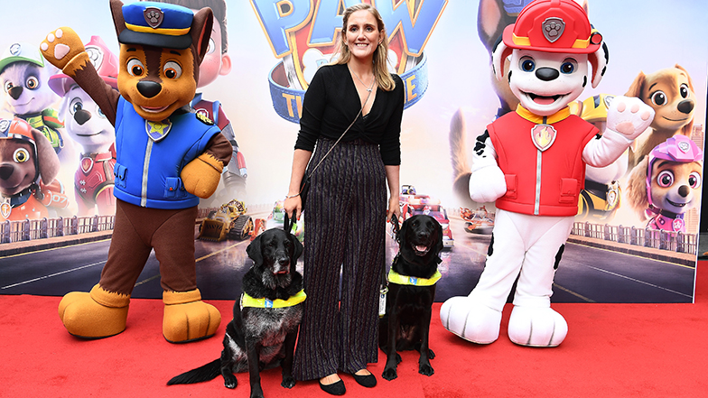 YouTuber Siobhan Meade with her guide dog Marty (right) and her partner's guide dog, Sammy, on the red carpet with Paw Patrol characters Chase (left) and Marshall.