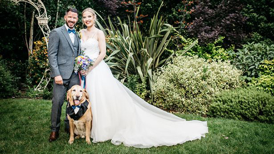 Bride Stacey with groom Kierran smiling with guide dog Toffee