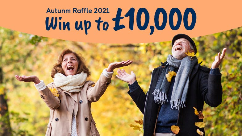 Man and women holding their hands up and looking up to a banner saying Win up to £10,000