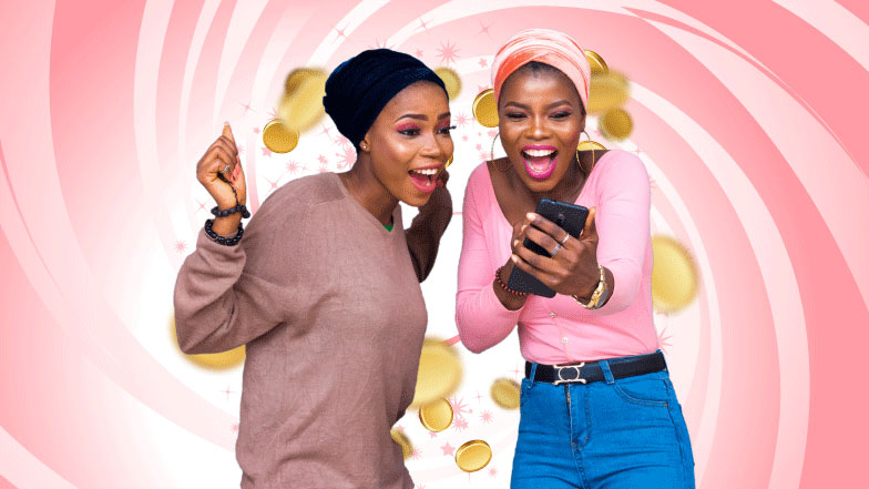 2 ladies looking at a phone and smiling one with her hands in the air