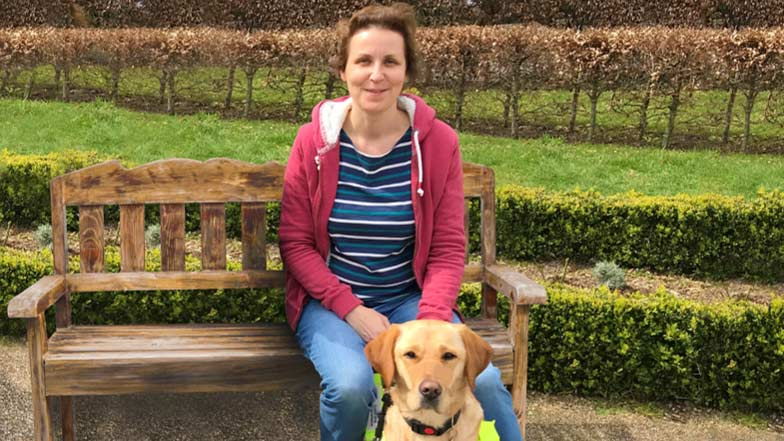 Katie sitting on a bench with guide dog Queenie at her feet