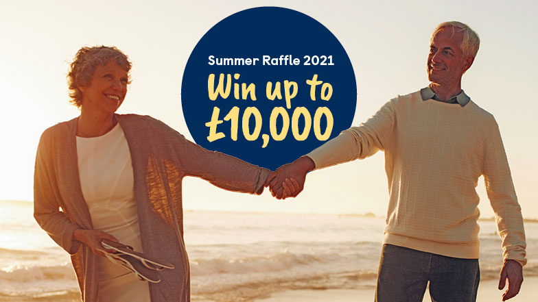 A couple holding hands on a beach an infographic displays Win up to £10000