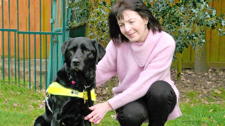 guide dog owner and guide dog sitting together outside