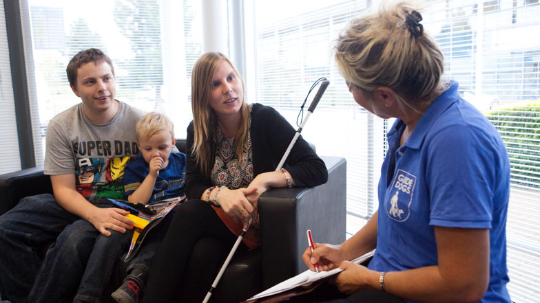 A guide dog employee helps a partially sighted person with a cane and her family