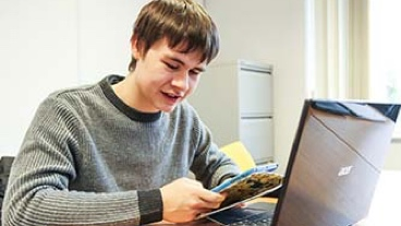 A teenager working at his laptop