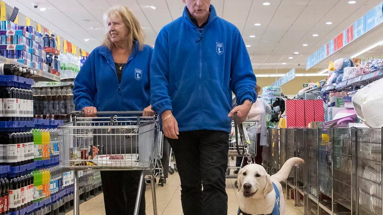 Eve walking next to her Guide Dogs trainers in a supermarket